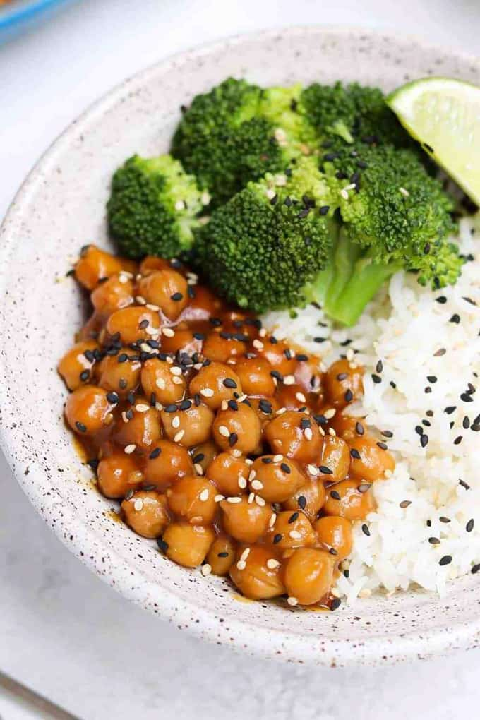 Sticky Sesame Chickpeas with white rice and broccoli in a white bowl with black sesame seeds on top
