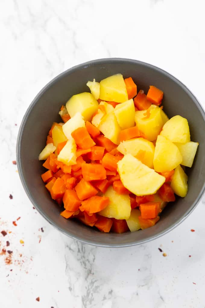 cooked potatoes and carrots in a grey bowl on a marble countertop
