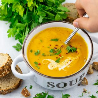 Vegan Pumpkin Soup in a white and brown bowl with a hand holding a spoon and a bunch of parsley in the background