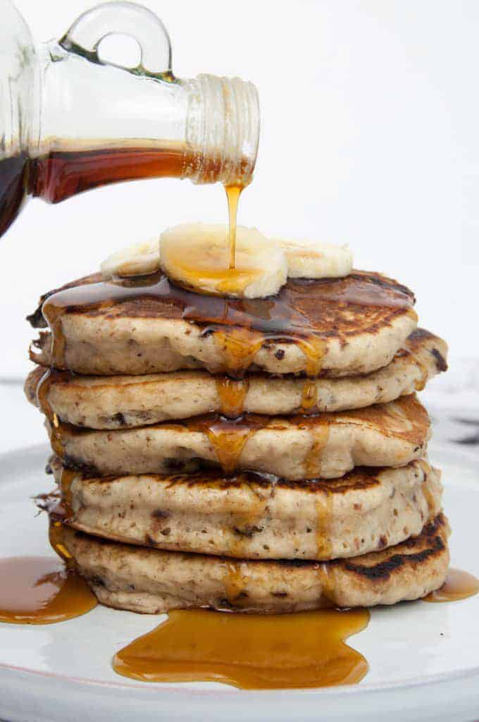 a stack of banana bread pancakes on a white plate with maple syrup being poured over the pancakes
