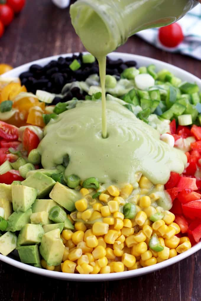 Mexican chopped salad in a bowl with avocado dressing being poured over the salad