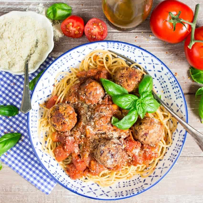 spaghetti with vegan meatballs in a white and blue plate on a wooden countertop with tomatoes, basil, and a small bowl of vegan parmesan in the background