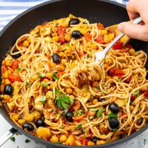 vegan spaghetti with chickpeas, olives, and artichokes hearts in a black pan with a wooden spoon on a marble countertop