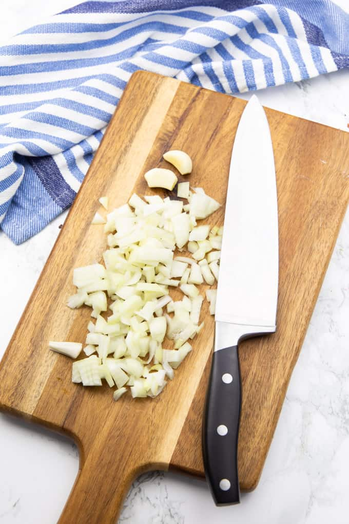 chopped onion and two cloves of garlic on a wooden chopping board with a large knife on the side