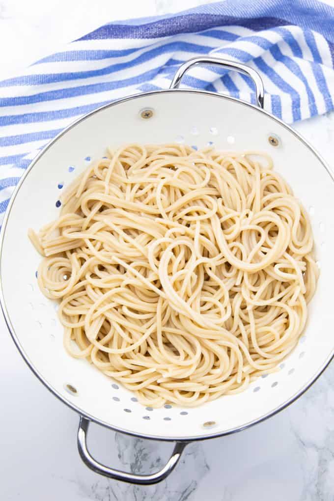 cooked spaghetti in a white colander on a marble countertop - Vegan Spaghetti