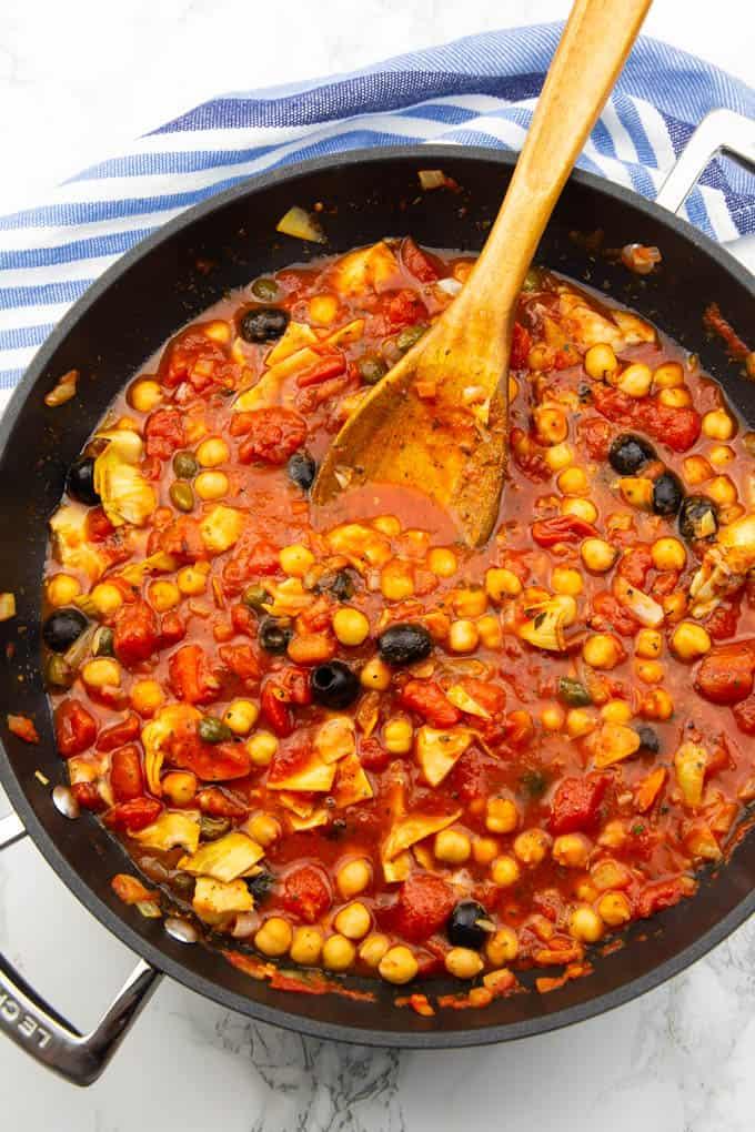 素食主义者意大利面条酱鹰嘴豆,黑橄榄,酸豆,和朝鲜蓟在一个黑色的锅上的大理石台面木勺