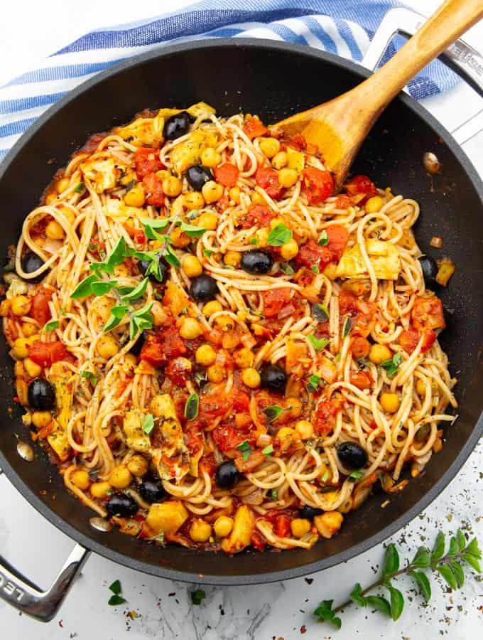 素食主义者面条与鹰嘴豆,橄榄和黑色锅朝鲜蓟心与一个大理石台面木勺