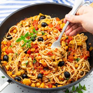Vegan Spaghetti with tomato sauce, chickpeas, and olives in a black pan on a marble countertop with a hand rolling up some of the spaghetti with a fork