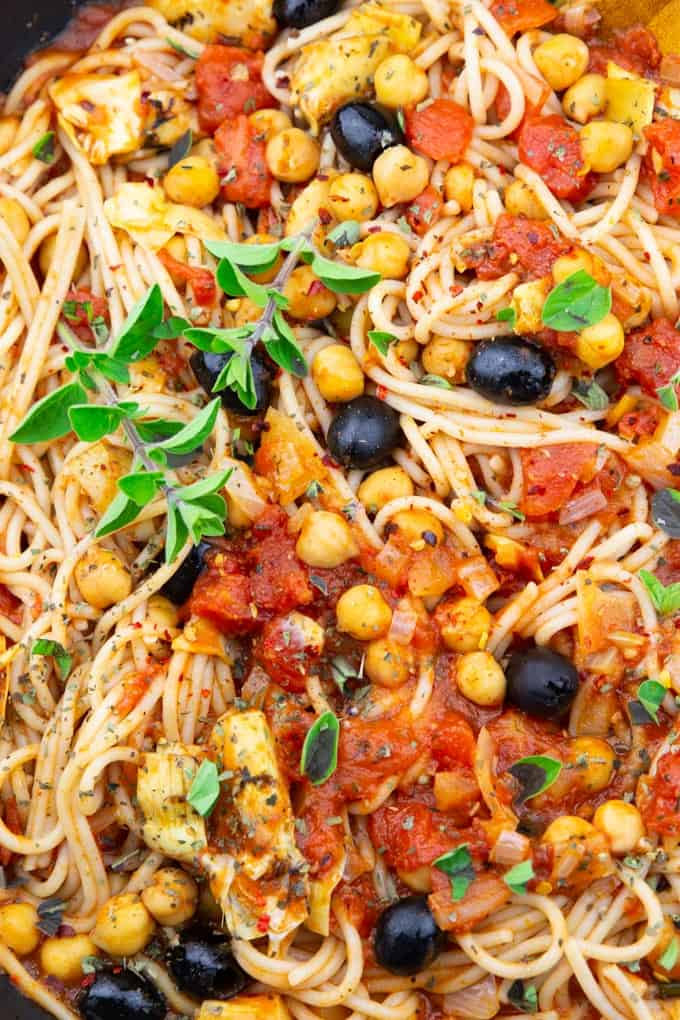 close-up photo of vegan spaghetti with chickpeas, olives, artichokes, and fresh oregano