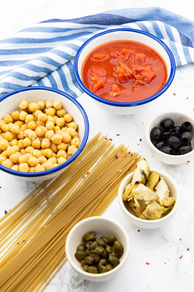 uncooked spaghetti and five bowls with diced tomatoes, cooked chickpeas, olives, artichokes, and capers on a marble countertop
