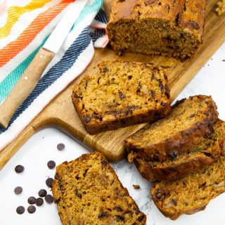 five vegan zucchini bread slices on a marble counter top with more zucchini bread on a wooden board in the background and chocolate chips on the side