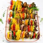 six grilled vegetable kabobs on a white plate on a marble countertop sprinkled with fresh herbs