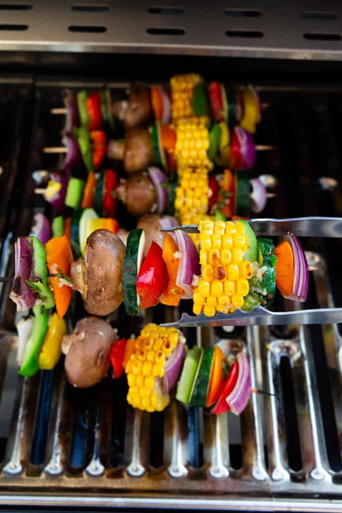six Vegetable Kabobs on a girl with one kabob being held with barbecue tongs