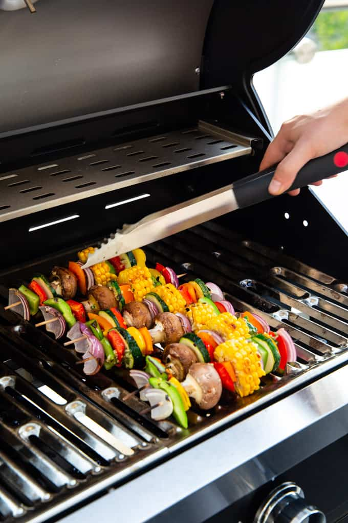 six Vegetable Kabobs on a grill with a hand holding barbecue tongs