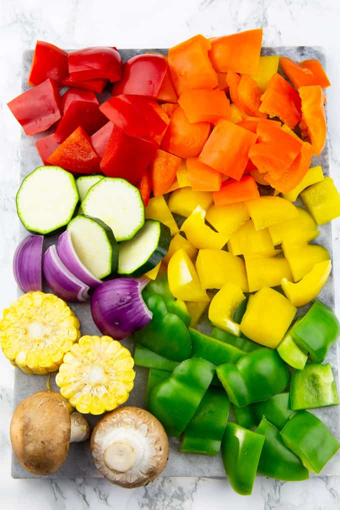 chopped bell peppers, zucchini, red onion, corn cobs, and mushrooms on a marble cutting board