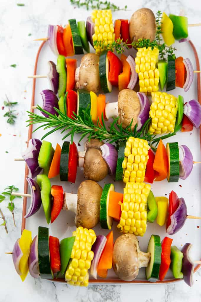 Vegetable Kabobs on a white plate on a marble countertop before grilling