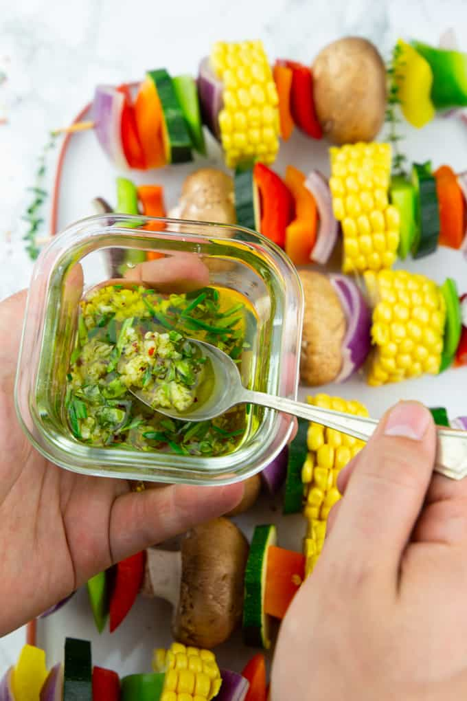 two hands holding a small bowl with garlic herb marinade and a spoon over a plate of vegetable kabobs