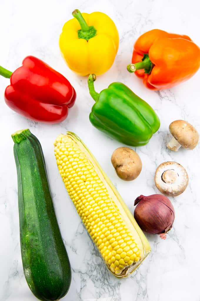 a red, orange, yellow, and green bell pepper, a zucchini, a corn cob, three mushrooms, and a red onion on a marble countertop