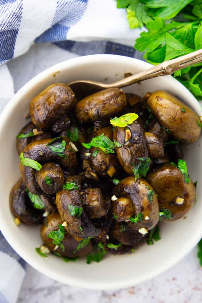 Balsamic Mushrooms in a white bowl with a fork on a marble countertop with a bunch of parsley in the background