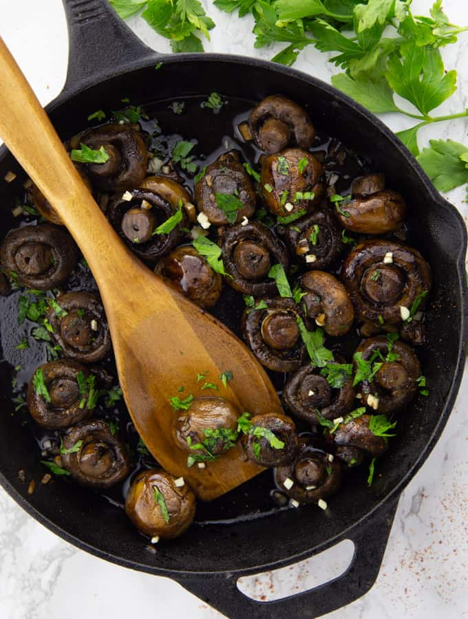 Balsamic Mushrooms in a cast iron pan with a wooden spoon on a marble countertop