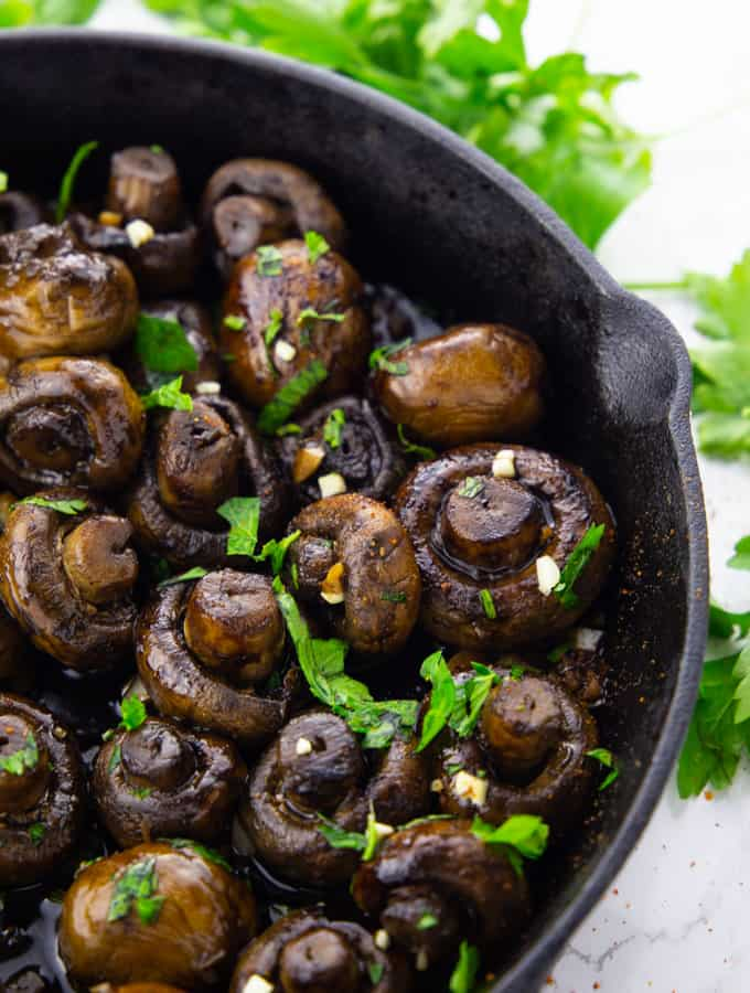 balsamic mushrooms in a cast iron pan sprinkled with chopped parsley on a marble countertop