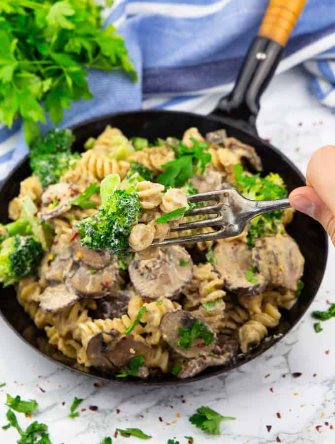 Broccoli Pasta in a black pan with a hand picking up some of the pasta with a fork