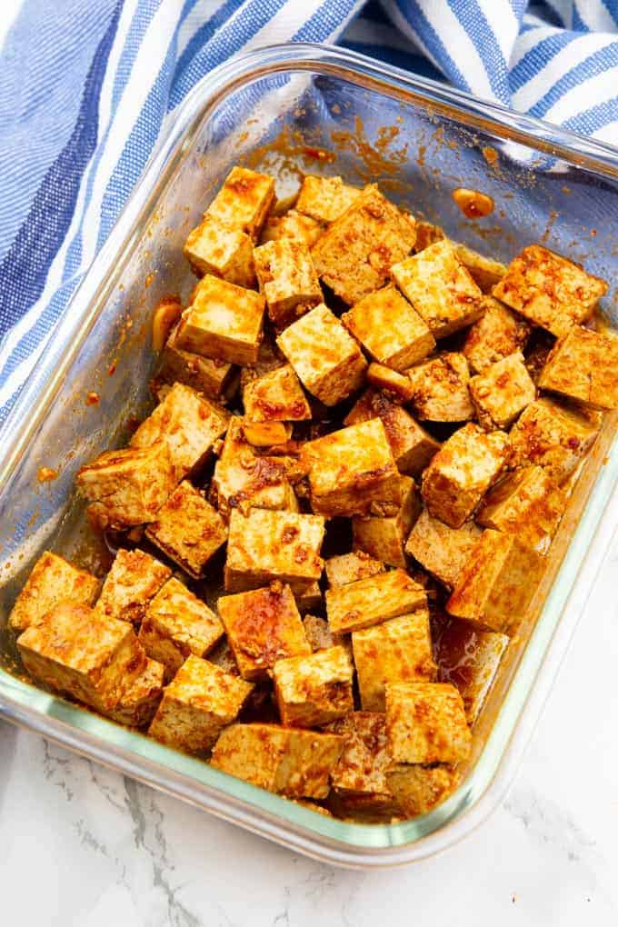 marinated tofu cubes in glass bowl on a marble countertop