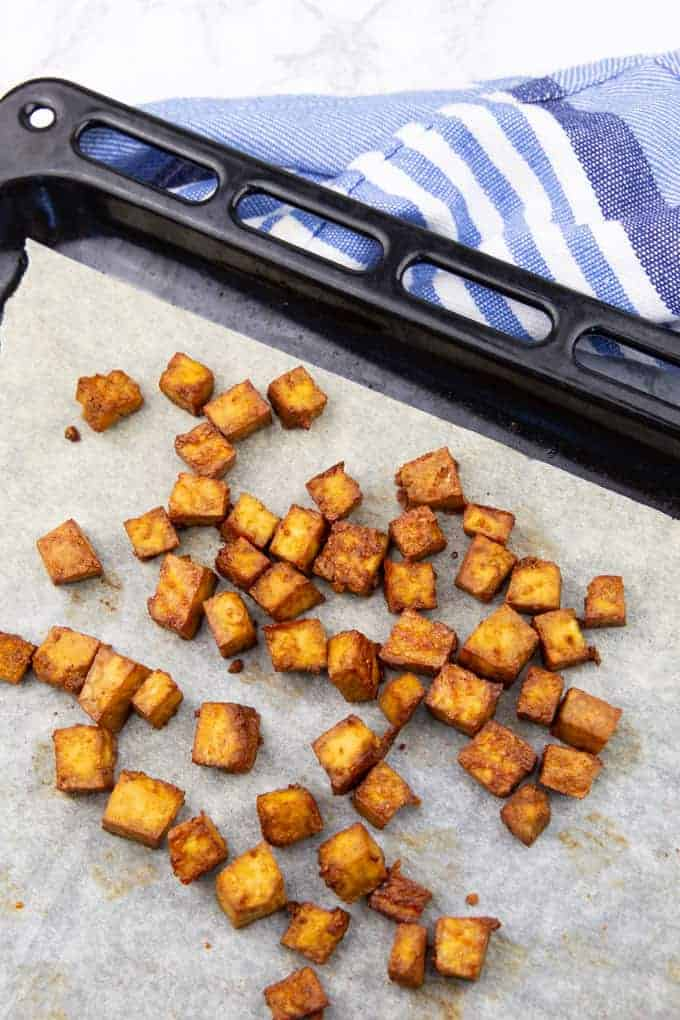 baked tofu cubes on a baking sheet lined with parchment paper