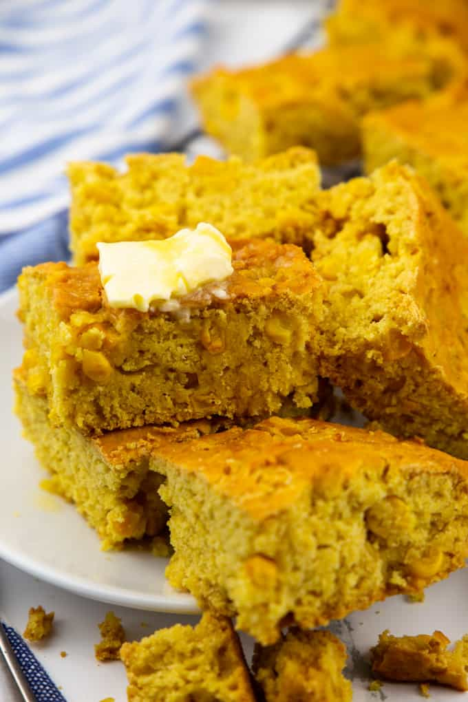 a stack of vegan cornbread squares with butter on top on a white plate