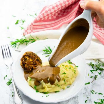 a hand pouring vegan gravy out of a sauce boat over mashed potatoes on a white plate with fresh herbs and a fork on the side