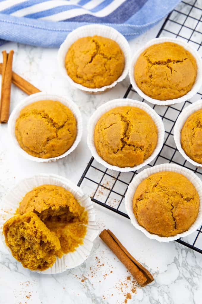 seven pumpkin muffins on a cooling rack on a marble countertop
