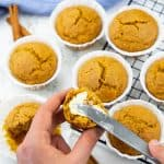 a hand spreading butter on a pumpkin muffin with a knife with more vegan pumpkin muffins in the background