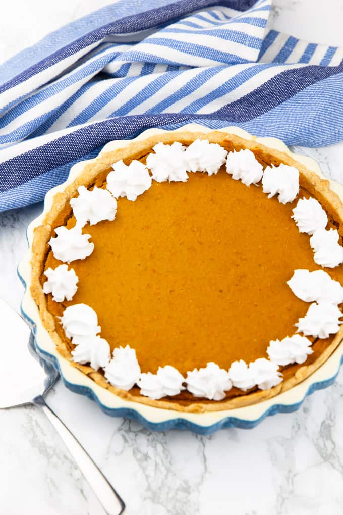 Vegan Pumpkin Pie in a blue baking form decorated with whipped cream on a marble countertop