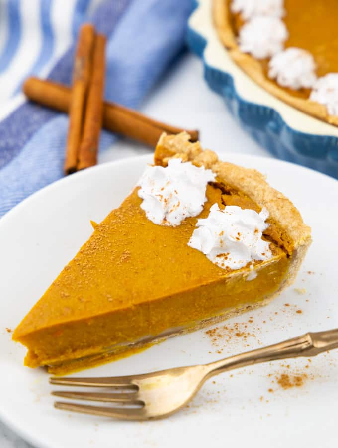 a slice of vegan pumpkin pie decorated with whipped cream on a white plate with a fork on the side