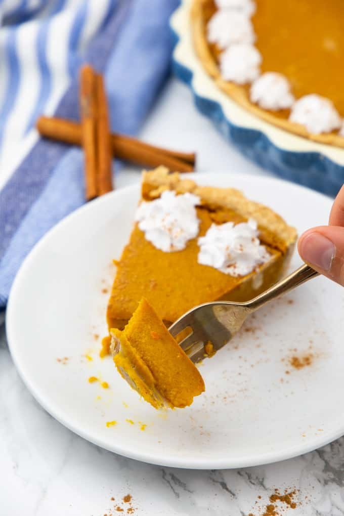 a slice of vegan pumpkin pie on a white plate with a hand picking up a piece of pie with a golden fork