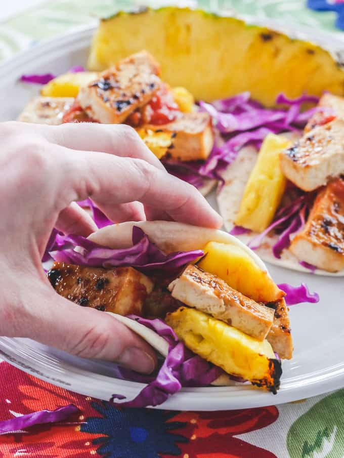 a hand holding Hawaiian Tofu Tacos with Grilled Pineapple on a white plate