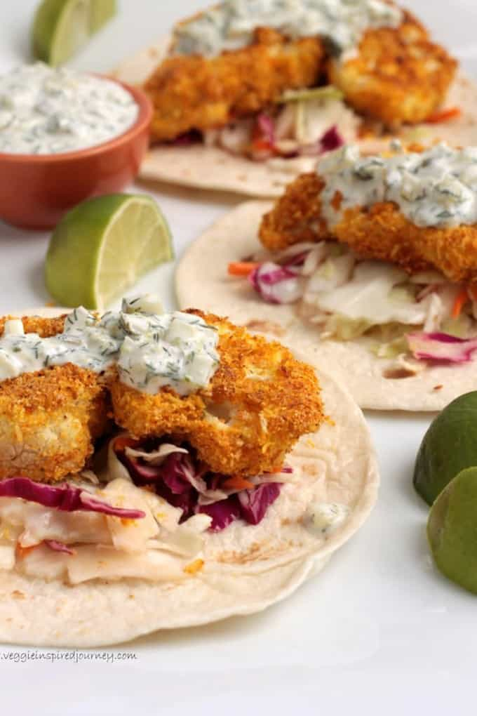 three crispy baked cauliflower tacos on a white countertop with limes on the side