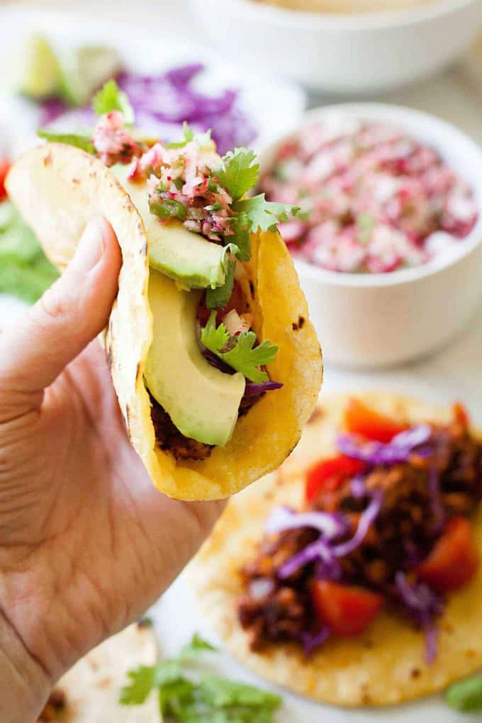a hand holding a vegan taco with tempeh and avocado with more tacos and bowls with filling in the background