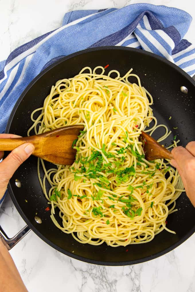 spaghetti aglio e olio in a large pan with two hands stirring everything with two wooden spoons