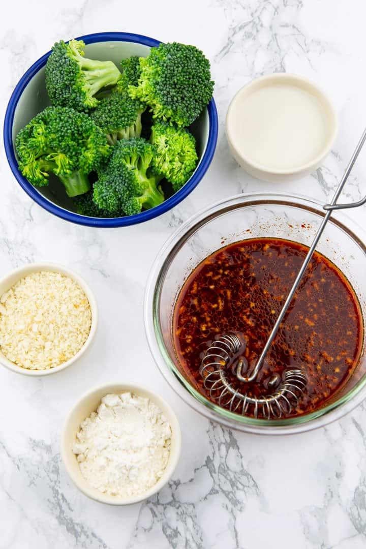 five bowls with broccoli florets, homemade gochujang sauce, almond milk, flour, and panko flakes on a marble countertop