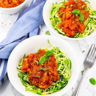 two bowls of zoodles with homemade marinara sauce on a marble countertop with a fork on the side