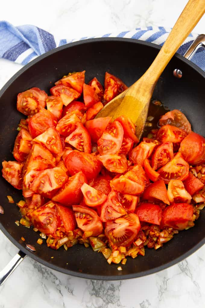 freshly diced tomatoes in a black pan with a wooden spoon on a marble countertop