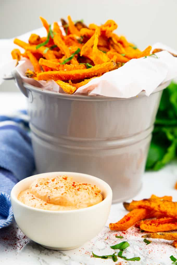 sweet potato fries in a bucket lined with parchment paper and a small bowl of Cajun sriracha mayonnaise in the front with some fries on the side