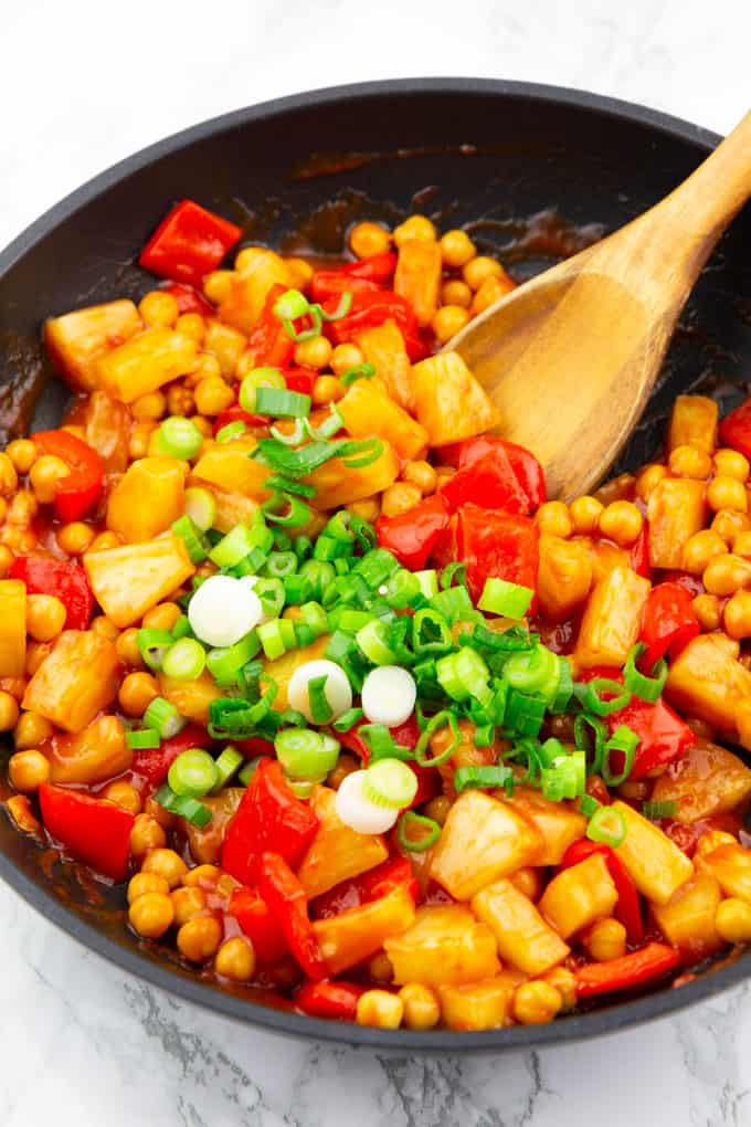 Sweet and Sour Chickpeas with chopped green onions on top in a black pan on a marble countertop