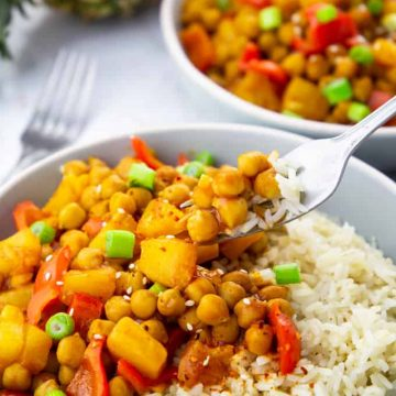 Two Bowls of Sweet and Sour Chickpeas over Rice on a marble countertop with a fork picking up some of the chickpeas