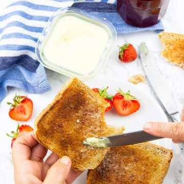 a hand holding a toast and spreading vegan butter on with strawberries and jam in the background