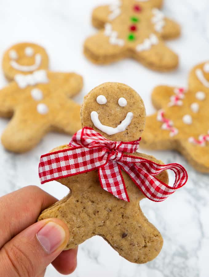 a hand holding a vegan gingerbread man with three more cookies in the background