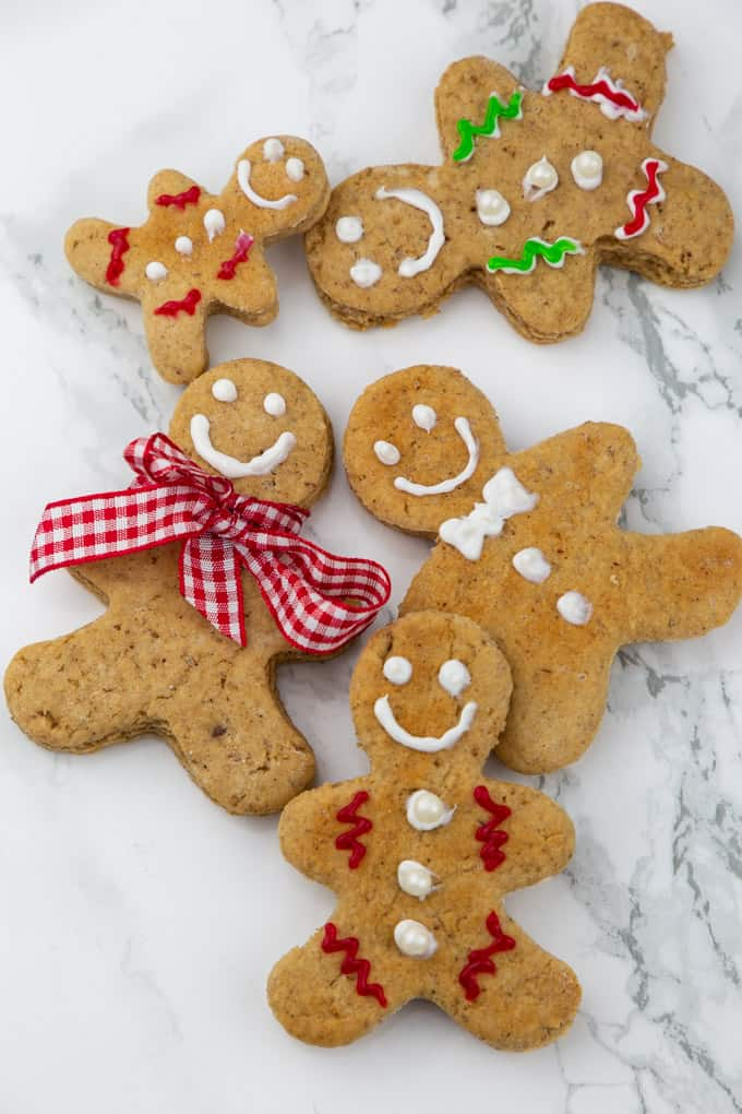 five vegan gingerbread cookies decorated with white, red, and green icing on a marble countertop