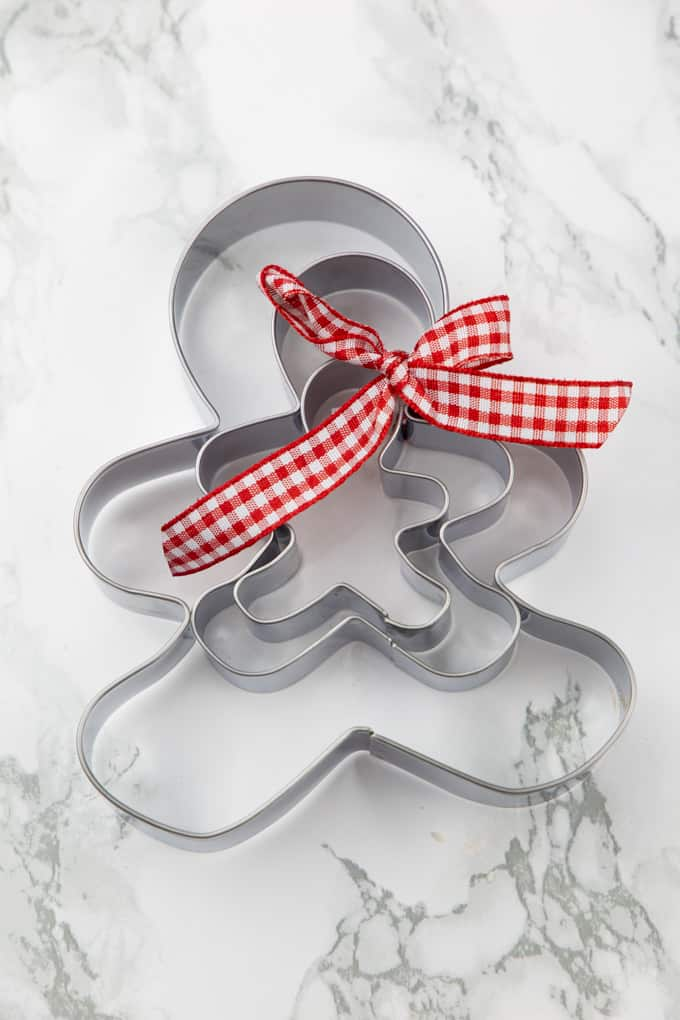 three gingerbread men cookie cutter with a red ribbon on a marble countertop