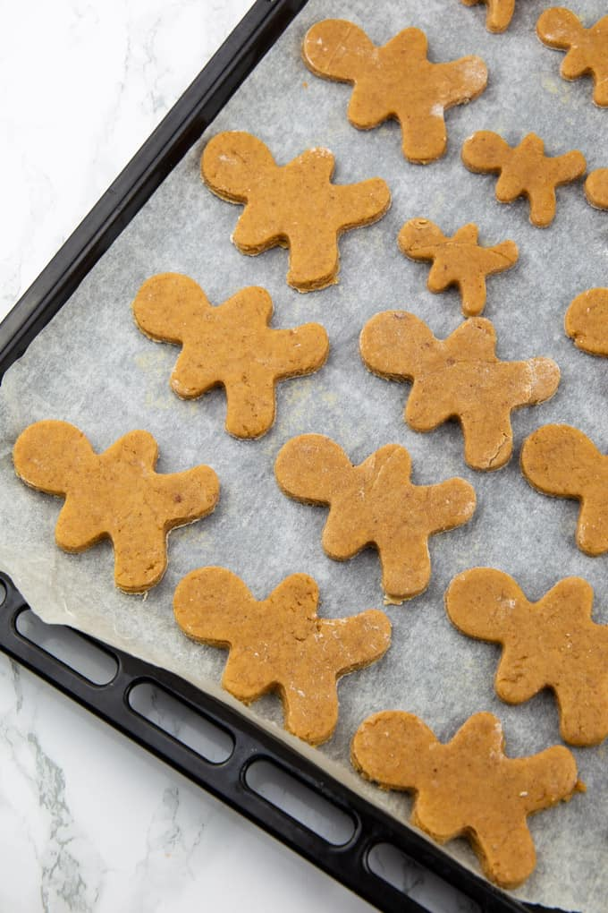Vegan Gingerbread Cookies on a baking sheet lined with parchment paper on a marble countertop